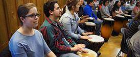 A row of people sitting in chairs, with tall drums on their laps.