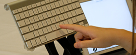 A child's hand reaches to type on an apple keyboard.