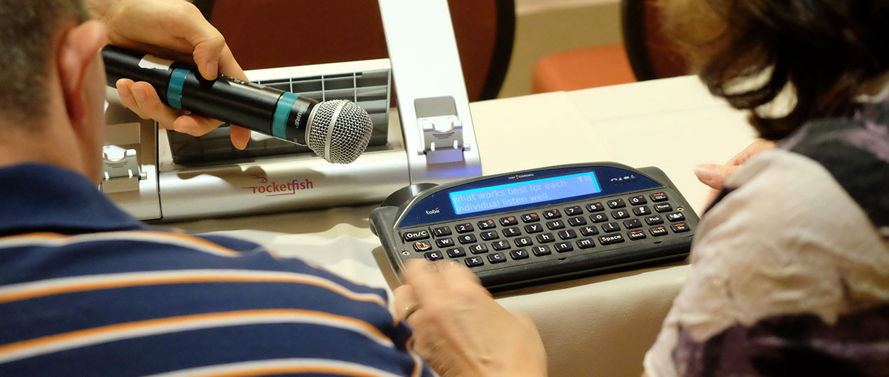A microphone is held up to a communication device as a woman types on the device